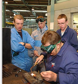 students watching teacher weld